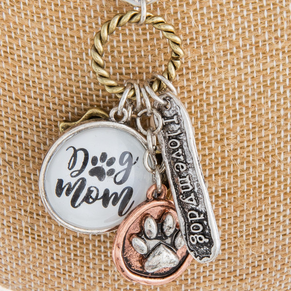 "Long metal necklace featuring multi ""Dog Mom"" hanging charms with a pearl accent and a toggle clasp. Pendant approximately 2"". Approximately 36"" in length."