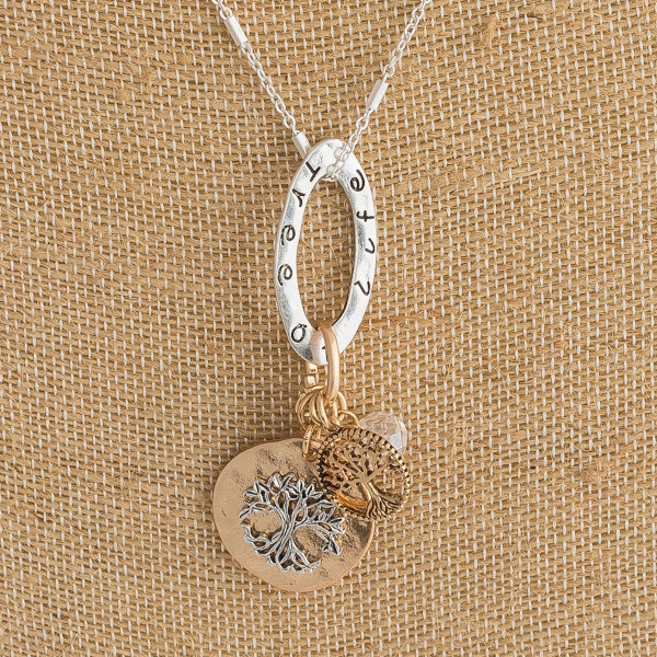 "Silver chain necklace featuring Tree of Life accents, faux pearl and bead details, and an oval pendant engraved with the phrase ""Tree of Life"". Approximately 24"" in length."