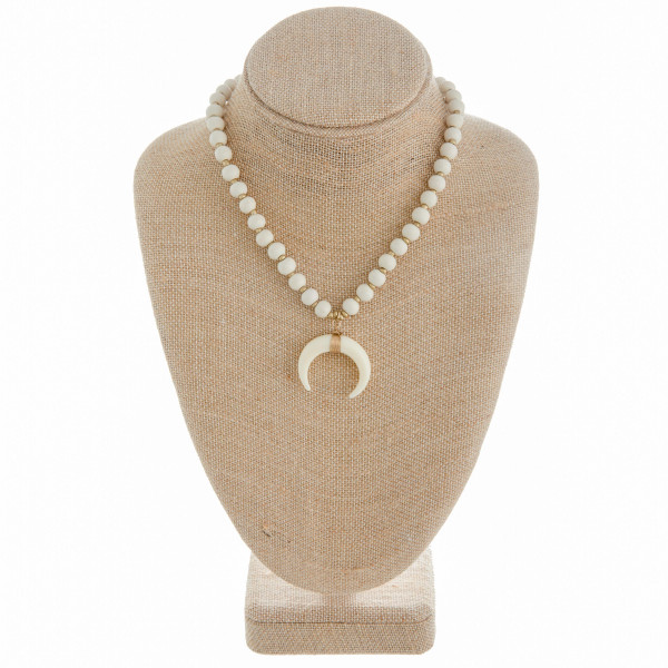 "Short wooden bead necklace featuring a crescent pendant. Approximately 16"" in length."