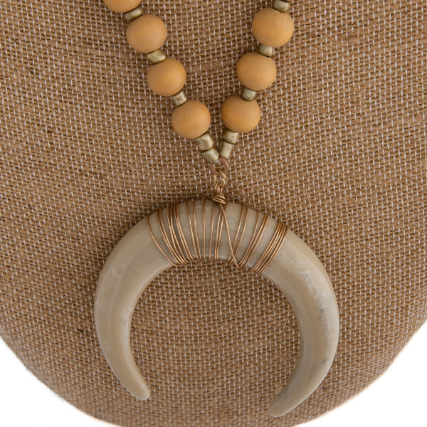 "Long beaded necklace featuring a crescent pendant and gold accents. Approximately 40"" in length. Pendant is approximately 2"" in diameter."
