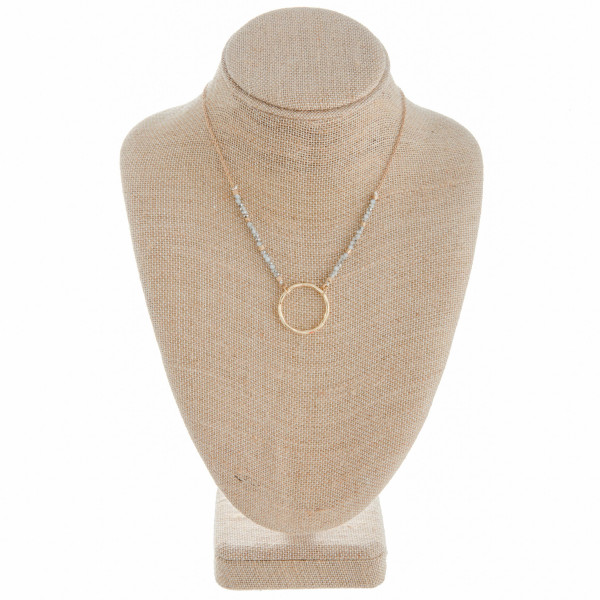 "Gold metal necklace featuring a circular pendant and beaded details. Approximately 16"" in length."