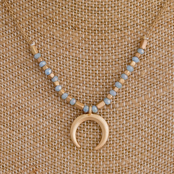 """Gold metal necklace featuring a crescent pendant with beaded details. Approximately 16"""" in length."""