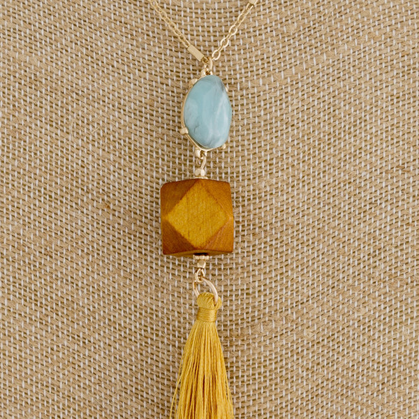 "Long gold chain necklace featuring a natural stone, wood, and tassel accents. Pendant approximately 5"". Approximately 38"" in length."