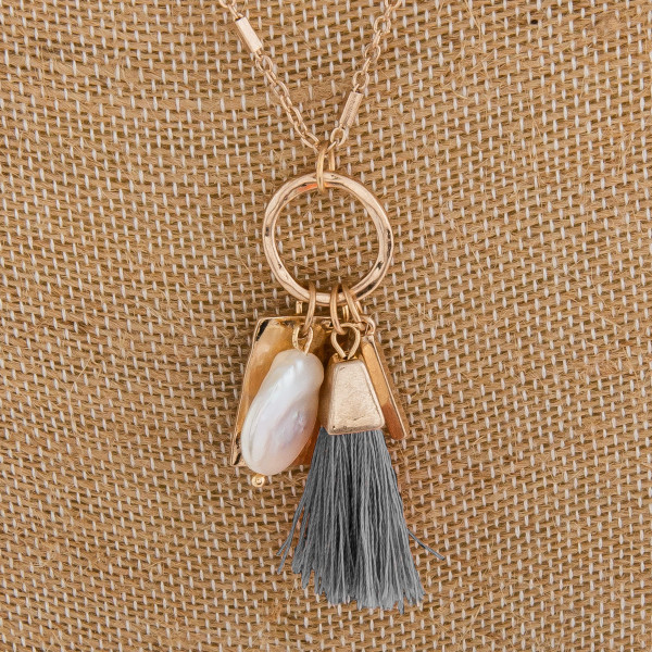 """Long metal necklace with small tassel and pearl charms. Approximate 32"""" in length."""