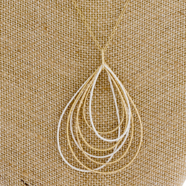 "Long gold chain necklace featuring a teardrop pendant with silver accents. Measures approximately 36"" in length."