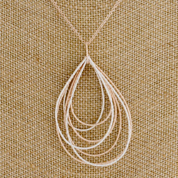 "Long rose gold chain necklace featuring a teardrop pendant with silver accents. Measures approximately 36"" in length."