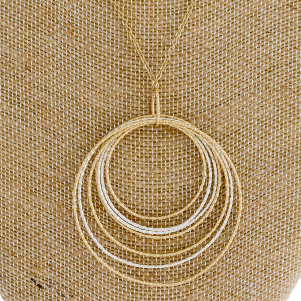 "Long gold chain necklace featuring a circular pendant with silver accents. Measures approximately 36"" in length."