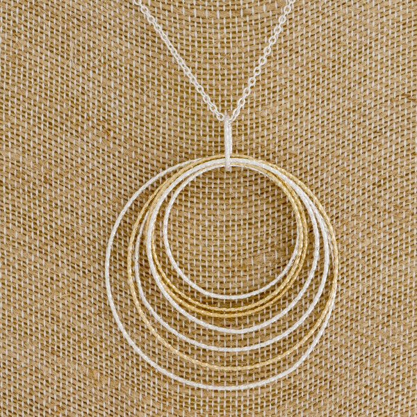 "Long silver chain necklace featuring a circular pendant with gold accents. Measures approximately 36"" in length."