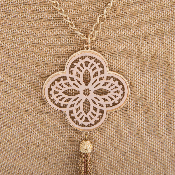 "Long necklace featuring a nude filigree pattern pendant with a tassel detail. Pendant approximately 6"" in length. Approximately 44"" in length overall."