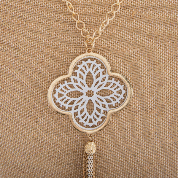 "Long necklace featuring a white filigree pattern pendant with a tassel detail. Pendant approximately 6"" in length. Approximately 44"" in length overall."