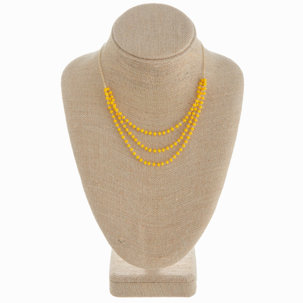 "Gold chain necklace featuring a three layered beaded detail. Approximately 16"" in length."