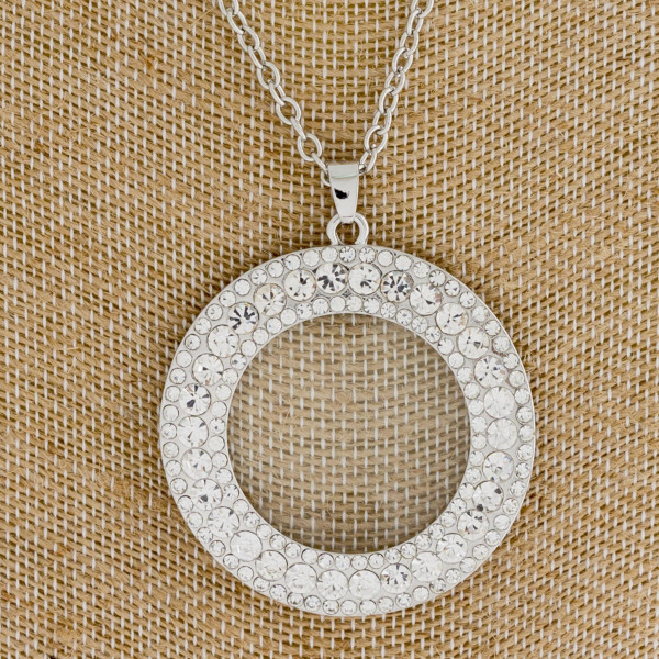 "Long silver necklace featuring a circular rhinestone pendant. Approximately 36"" in length. Pendant is approximately 2"" in diameter."