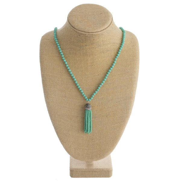 "Long beaded necklace featuring a beaded tassel pendant with faceted bead details. Pendant approximately 3"". Approximately 38"" in length overall."