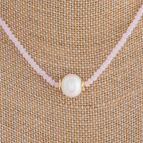 "Short pink beaded necklace featuring a pearl accent. Measures approximately 16"" in length."