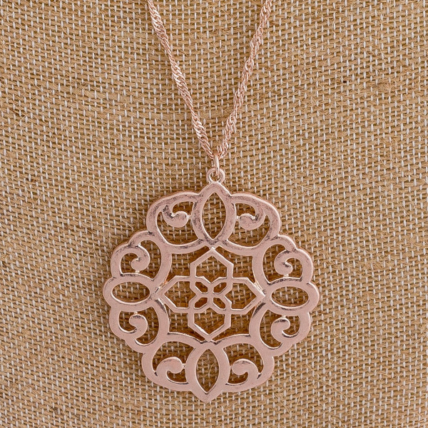 "Long rose gold chain necklace featuring a filigree pendant. Approximately 36"" in length."