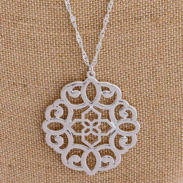 "Long silver chain necklace featuring a filigree pendant. Approximately 36"" in length."