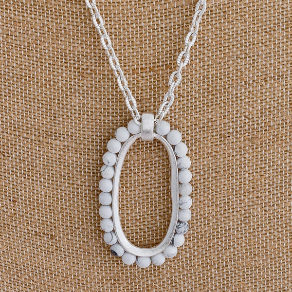 "Long silver necklace featuring an oblong pendant with beaded accents. Pendant approximately 2"". Approximately 34"" in length overall."