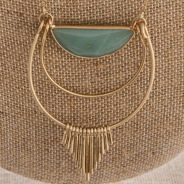 "Long metal necklace featuring a mint colored natural stone pendant with gold tassel accents. Pendant approximately 2.75"". Approximately 36"" in diameter."