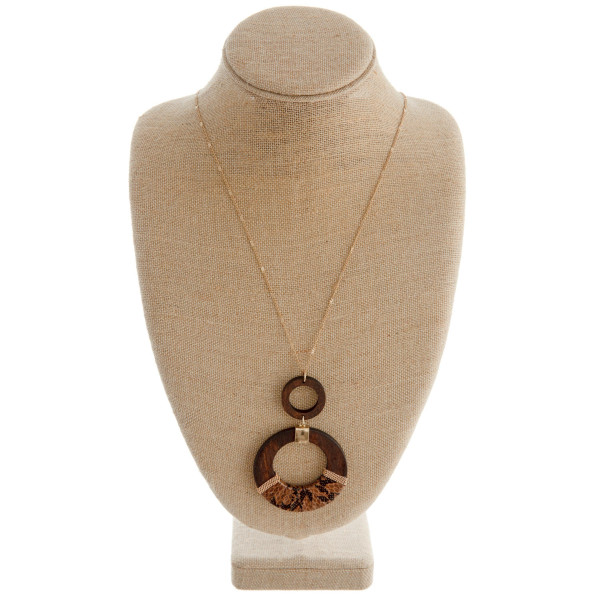 "Long gold chain necklace featuring a circular pendant with faux leather animal print accents. Pendant approximately 4"" in length. Approximately 42"" in length."