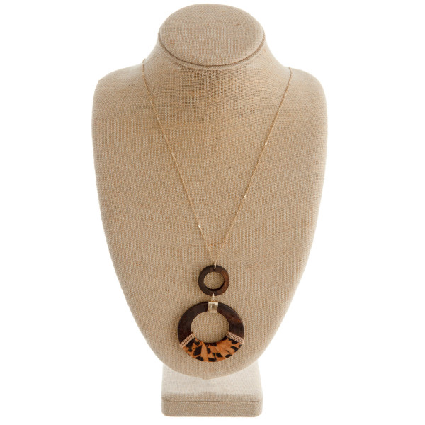 """Long gold chain necklace featuring a circular pendant with faux leather animal print accents. Pendant approximately 4"""" in length. Approximately 42"""" in length."""