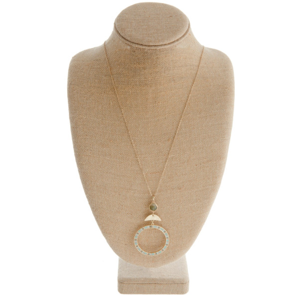 Gold metal necklace featuring a circular pendant with resin detail  stone accent