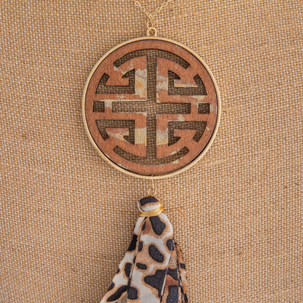 "Long gold chain necklace featuring a circular pendant with wood detailing and a fabric cheetah print tassel. Approximately 36"" in length. From pendant to end of tassel is approximately 9""."