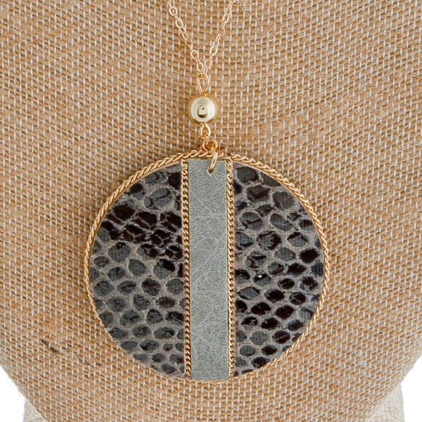 """Long dainty cable chain necklace featuring a faux leather snakeskin disc pendant with gold chain inspired accents. Pendant approximately 2"""" in diameter. Approximately 34"""" in length overall."""