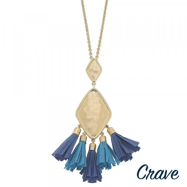 "Long metal necklace featuring a gold pendant with blue raffia tassel accents. Pendant approximately 3.5"". Approximately 38"" in length."
