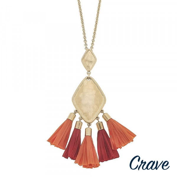 "Long metal necklace featuring a gold pendant with coral raffia tassel accents. Pendant approximately 3.5"". Approximately 38"" in length."