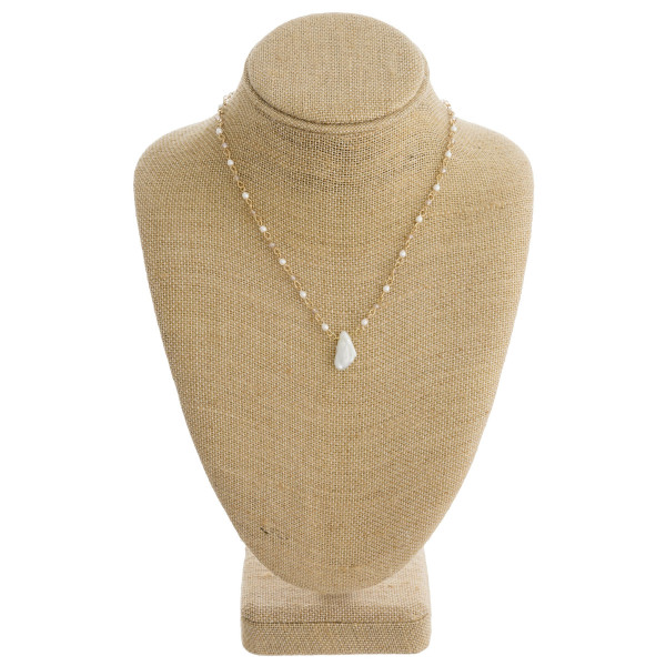 """Long metal necklace featuring faceted bead and pearl details and a freshwater pearl accent. Approximately 18"""" in length."""