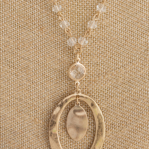 "Gold metal necklace featuring a oval pendant with beaded details. Pendant approximately 2"". Approximately 24"" in length."