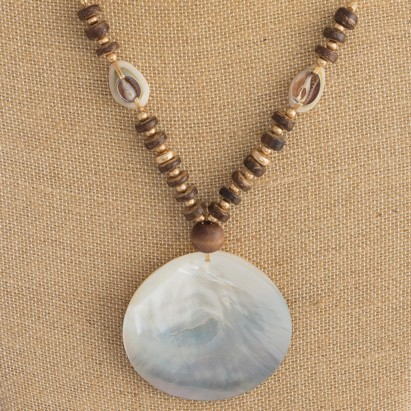 "Long gold chain necklace featuring bead and puka shell accents, and a black mother of pearl inspired disc. Approximately 36"" in length."