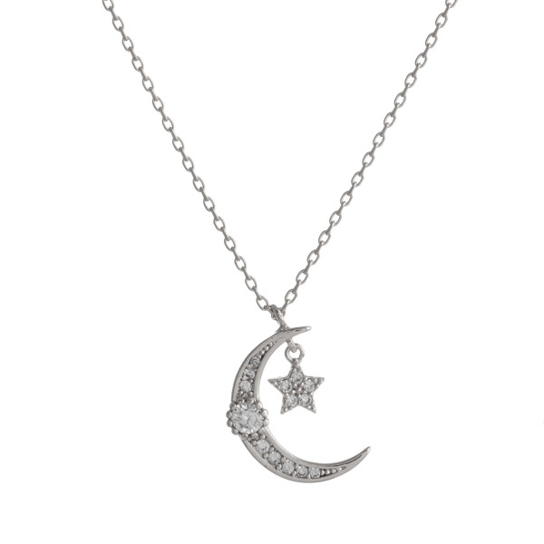 "Dainty silver chain necklace featuring a cubic zirconia adorned crescent pendant and a star accent. Approximately 18"" in length. Pendant is approximately 1"" in diameter."
