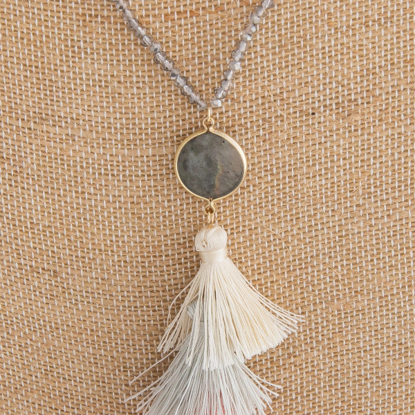 "Long gold chain necklace with gold and glass bead details featuring a labradorite stone and a fanned tassel. Measures approximately 36"" in length."