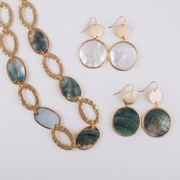"""Long black mother of pearl circular earrings with brass detail. Measures approximately 2"""" long."""
