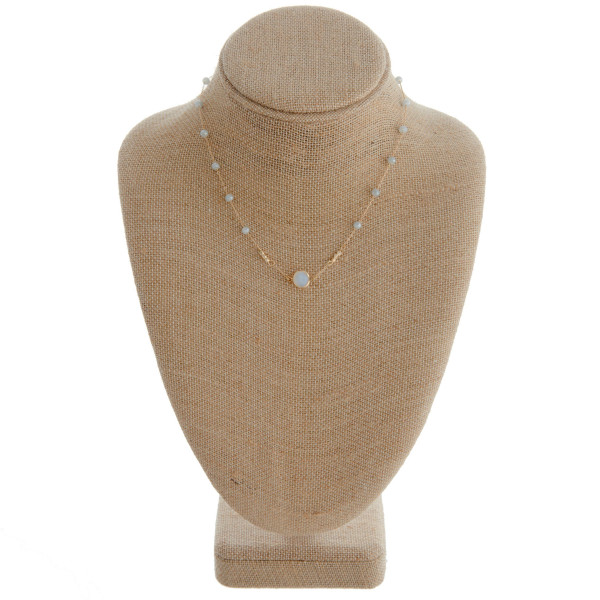"Short grey beaded necklace featuring a natural stone detail. Measures approximately 16"" in length."