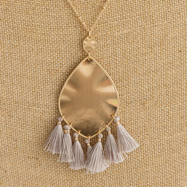 "Long metal necklace featuring a metal plated teardrop pendant with tassel details and gold accents. Pendant approximately 3"". Approximately 36"" in length overall."