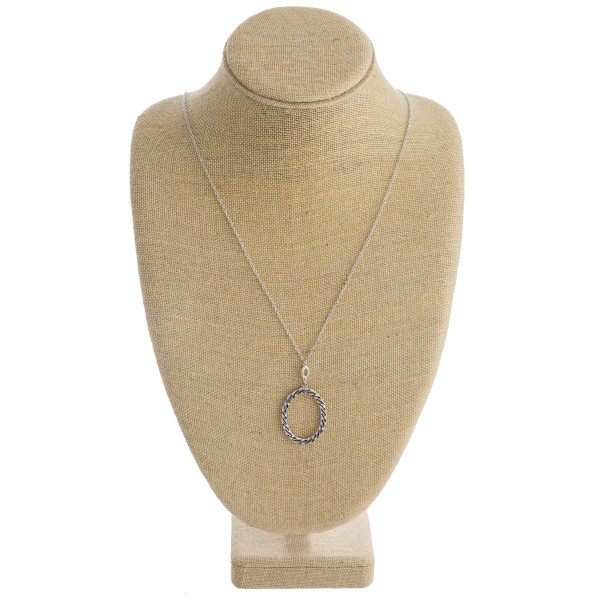"""Long metal necklace featuring a oval pendant with twisted details. Pendant approximately 2"""". Approximately 36"""" in length overall."""