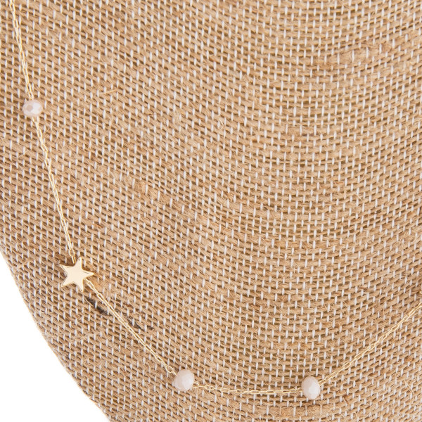 "Long gold chain necklace featuring beaded detail and star accents. Approximately 34"" in length."