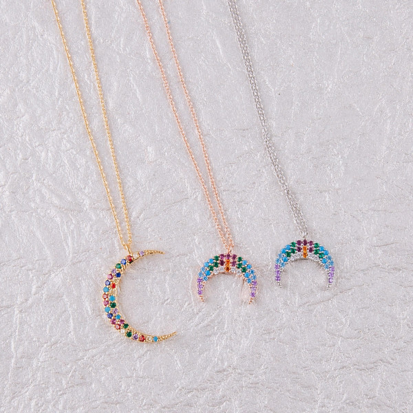 """Dainty metal necklace featuring a crescent pendant with multicolor cubic zirconia details. Pendant approximately .5"""". Approximately 18"""" in length overall."""