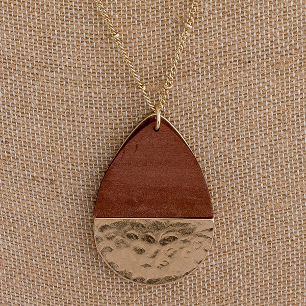 """Long necklace featuring a teardrop inspired pendant with wood and metal plated details. Pendant approximately 2"""". Approximately 36"""" in length overall."""