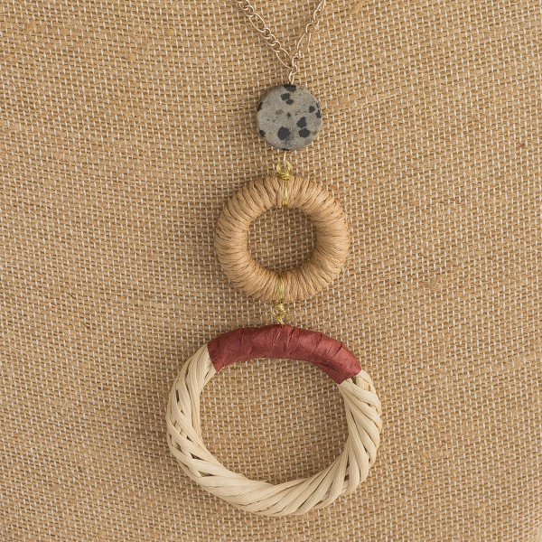 "Long figaro chain necklace featuring a rattan woven double circular pendant with raffia wrapped details and a resin accent. Pendant approximately 4"". Approximately 38"" in length overall."