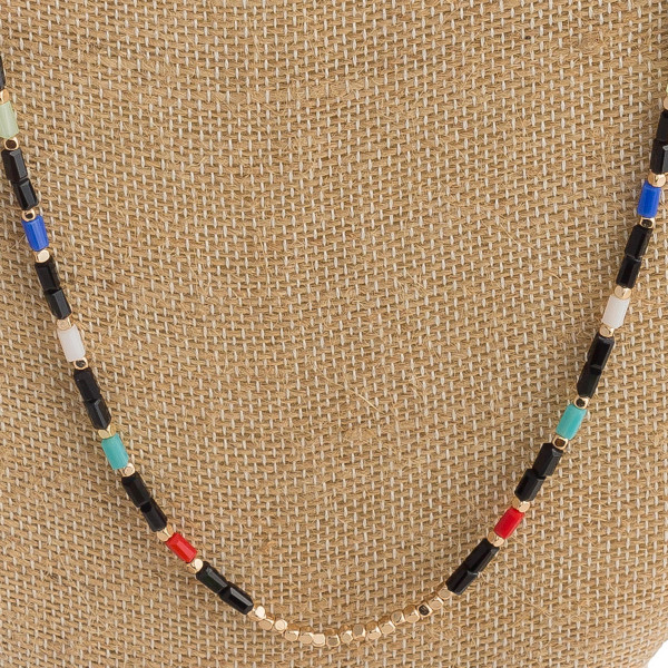 "Long beaded necklace featuring gold details and multicolored accents. Approximately 30"" in length."
