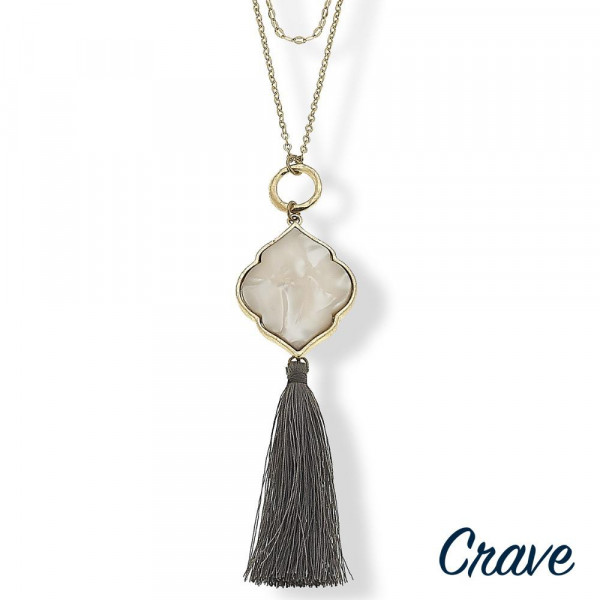 "Long double layered necklace featuring a resin inspired pendant with a tassel accent. Pendant approximately 5"". Approximately 39"" in length overall."