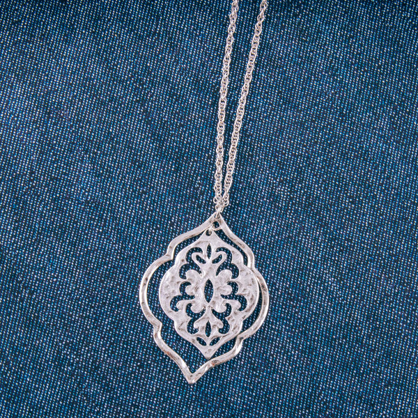"Long metal necklace featuring a lotus inspired pendant with a center pattern detail. Pendant approximately 2.25"". Approximately 34"" in length overall."