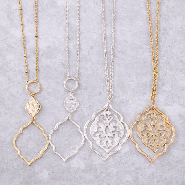 "Long metal necklace featuring a lotus inspired pendant. Pendant approximately 3"". Approximately 36"" in length overall."