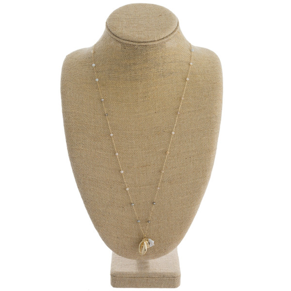 "Long dainty cable chain necklace featuring faceted bead details with a pearl, puka shell, and seashell accent. Approximately 28"" in length."