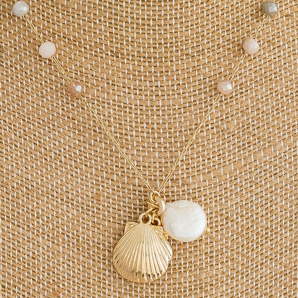 "Dainty metal necklace featuring natural faceted bead details with seashell, and pearl accents. Approximately 16"" in length."