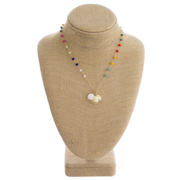 "Dainty metal necklace featuring multicolor faceted bead details with seashell, and pearl accents. Approximately 16"" in length."