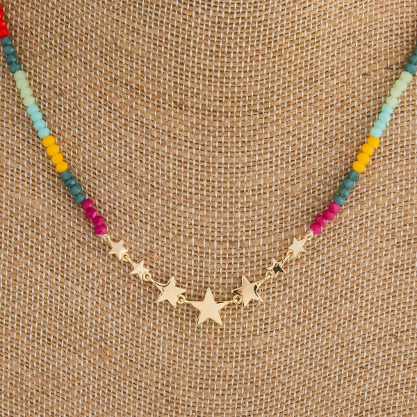 "Iridescent beaded necklace featuring gold star center accents. Approximately 16"" in length."